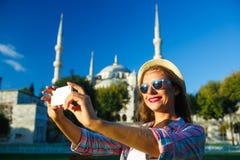 Menina que faz o selfie pelo smartphone no fundo do Bl Fotografia de Stock