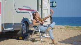 Menina que faz o selfie perto de seu campista Mulher de viagem pela camionete de campista móvel da roulotte rv filme