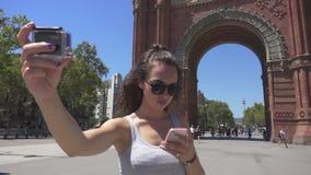 Menina que faz o vídeo dsi mesma na câmera da ação Turista da mulher perto do arco de Barcelona filme