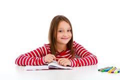 Menina que faz os trabalhos de casa isolados no fundo branco Fotografia de Stock Royalty Free