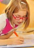 Menina que faz trabalhos de casa em casa Imagens de Stock Royalty Free