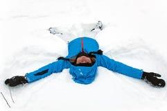 Menina que faz um anjo da neve do inverno Fotografia de Stock Royalty Free