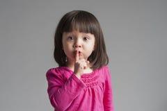 Menina que faz um gesto do silêncio do mantimento Imagem de Stock