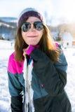 Menina que faz uma cara engraçada que inclina-se em esquis Imagem de Stock