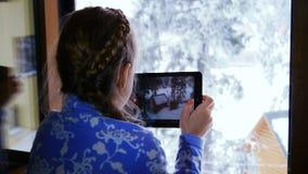 Menina que faz uma foto usando a tabuleta filme