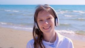 A menina que feliz do retrato as caminhadas escutam música nos fones de ouvido agita a praia da areia do mar principal video estoque