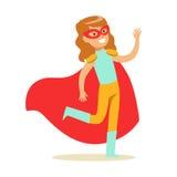 Menina que finge ter os poderes super vestidos no traje azul e amarelo do super-herói com cabo vermelho e mascarar o sorriso Fotografia de Stock
