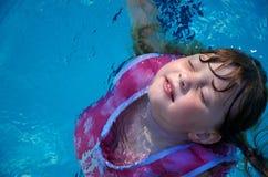 Menina que flutua na piscina foto de stock royalty free