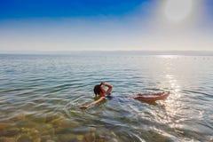 A menina que flutua na superfície do Mar Morto, Jordânia, aprecia suas férias Fotografia de Stock Royalty Free
