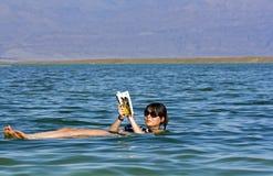 Menina que flutua no mar inoperante Fotografia de Stock Royalty Free