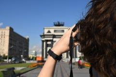 Menina que fotografa o arco triunfal em Moscou imagem de stock