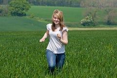 Menina que funciona através de um campo Fotografia de Stock