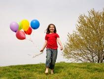 Menina que funciona com balões Imagens de Stock