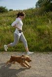 Menina que funciona com seu cão Fotos de Stock Royalty Free