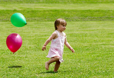 Menina que funciona em uma grama com balões Foto de Stock Royalty Free