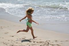 Menina que funciona na praia Fotografia de Stock