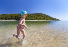 Menina que funciona no mar Fotos de Stock Royalty Free
