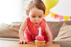 Menina que funde à vela no queque no aniversário Fotos de Stock Royalty Free