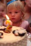 Menina que funde no bolo de aniversário Imagens de Stock