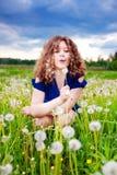 Menina que funde um dente-de-leão Imagens de Stock Royalty Free