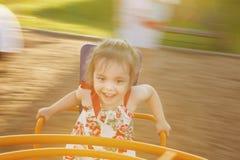 Menina que gira em um carrossel do ` s das crianças entre o campo de jogos Foto de Stock Royalty Free