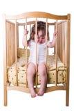 Menina que grita ao sentar-se na cama Fotografia de Stock Royalty Free