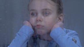 Menina que grita e que olha na janela em gotas da chuva, falta de sofrimento da atenção filme