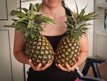 Menina que guarda abacaxis Imagens de Stock