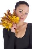 Menina que guarda as folhas de bordo alaranjadas do outono no branco imagem de stock
