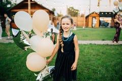 Menina que guarda balões no exterior Festa de anos Imagens de Stock Royalty Free