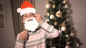 Menina que guarda bandeiras com o chapéu e a barba do ` s de Santa Fotos de Stock