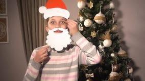 Menina que guarda bandeiras com o chapéu e a barba do ` s de Santa Fotografia de Stock