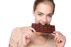 Menina que guarda a barra de chocolate grande em seus tooths fotografia de stock