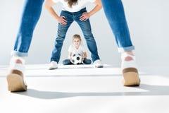 Menina que guarda a bola de futebol com pais na parte dianteira foto de stock