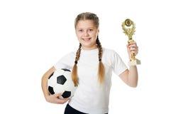 Menina que guarda a bola e o troféu do futebol Fotos de Stock