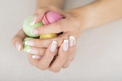 Menina que guarda bolinhos de amêndoa coloridos nas mãos com tratamento de mãos francês do gel Fotografia de Stock Royalty Free