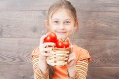 menina que guarda a cesta de vime com tomates vermelhos fotografia de stock royalty free