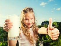 Menina que guarda de vidro com leite Fotos de Stock Royalty Free