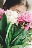 Menina que guarda e que cheira o ramalhete bonito do rosa e o branco das pe?nias na janela de madeira velha r?stica Decora??o flo imagem de stock royalty free