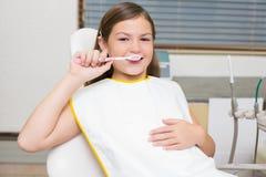 Menina que guarda a escova de dentes na cadeira dos dentistas Imagem de Stock Royalty Free