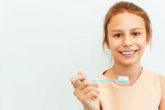 Menina que guarda a escova de Teeh Menina feliz que escova seus dentes imagem de stock