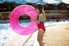 Menina que guarda a felicidade brincalhão da associação da boia da natação foto de stock