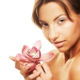 Menina que guarda a flor da orquídea em suas mãos Imagem de Stock Royalty Free