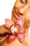 Menina que guarda a flor da orquídea em suas mãos Imagens de Stock Royalty Free