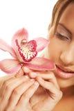 Menina que guarda a flor da orquídea em suas mãos Imagens de Stock