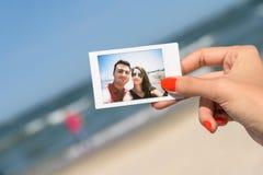 Menina que guarda a foto imediata de pares felizes Imagens de Stock Royalty Free