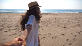 Menina que guarda a mão e o corredor masculinos na praia ao oceano Siga-me que o tiro da jovem mulher no chapéu puxa seu noivo no video estoque