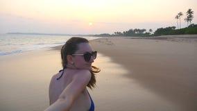 Menina que guarda a mão e o corredor masculinos na praia exótica tropical perto do oceano Siga-me tiro da jovem mulher para puxar video estoque