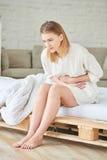 A menina que guarda o abdômen devido aos dias menstruais fotografia de stock royalty free