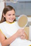 Menina que guarda o espelho na cadeira dos dentistas Fotos de Stock Royalty Free